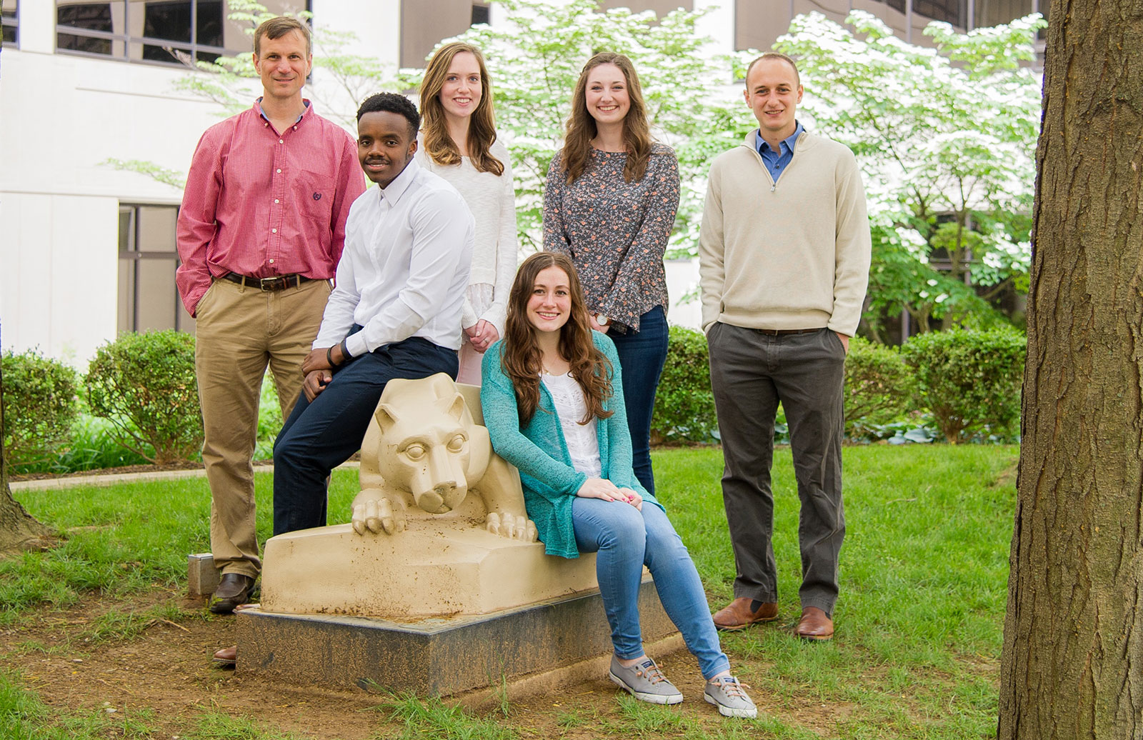Student participants in the American Heart Association Undergraduate Summer Fellowship are seen in 2018 with Program Director Dr. Christopher Yengo. The students and Dr. Yengo are pictured outdoors, with a tree behind them and a statue of Penn State's Nittany Lion mascot in front of them.