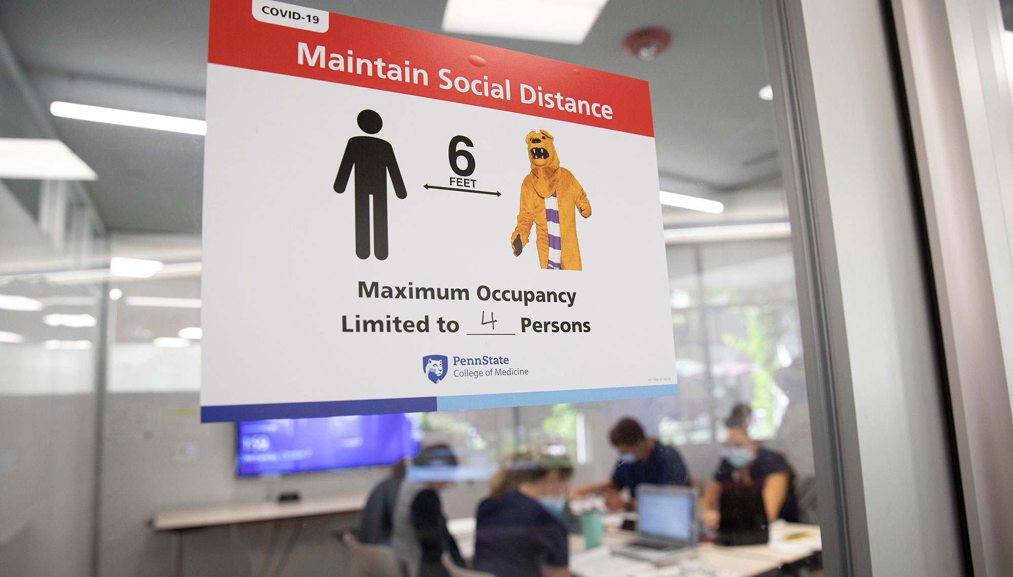 A sign noting a maximum occupancy of four people, and reminding people entering to stay six feet apart, appears on the door of a study room in Harrell Health Sciences Library in fall 2020. The precautions are due to COVID-19.