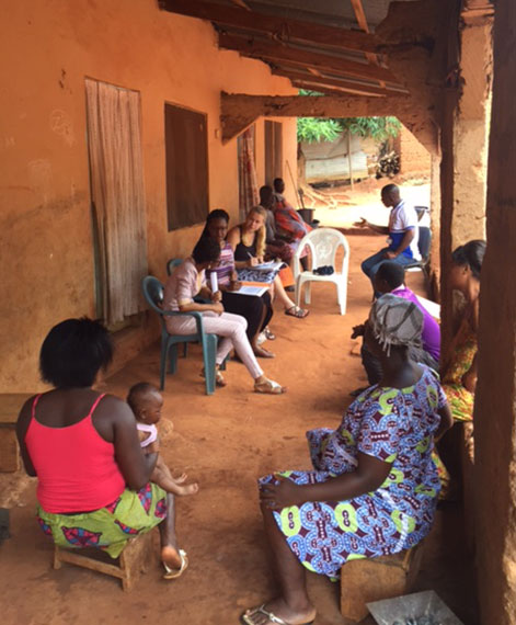 Students in the Global Health Scholars Program are pictured in June 2016 conducting nutritional surveys in Yilo Krobo, a rural town in the eastern region of Ghana, with a translator from a regional hospital. Among those pictured are students Annyella Douglas and Lynnette Lacek, who are seen sitting under a large rooftop overhang over a dirt floor, surrounded by Ghanaian community members.