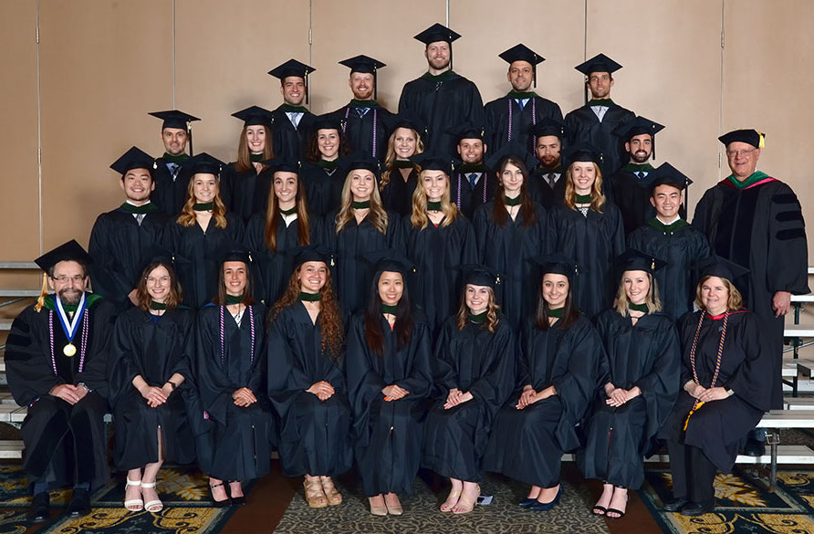 The first graduates of the Penn State College of Medicine Physician Assistant Program are pictured in five rows, with the first row sitting and the others standing behind them on stairs or risers, in June 2016.