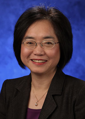 A portrait photograph of Dr. Shou Ling Leong smiling in front of a blue background.