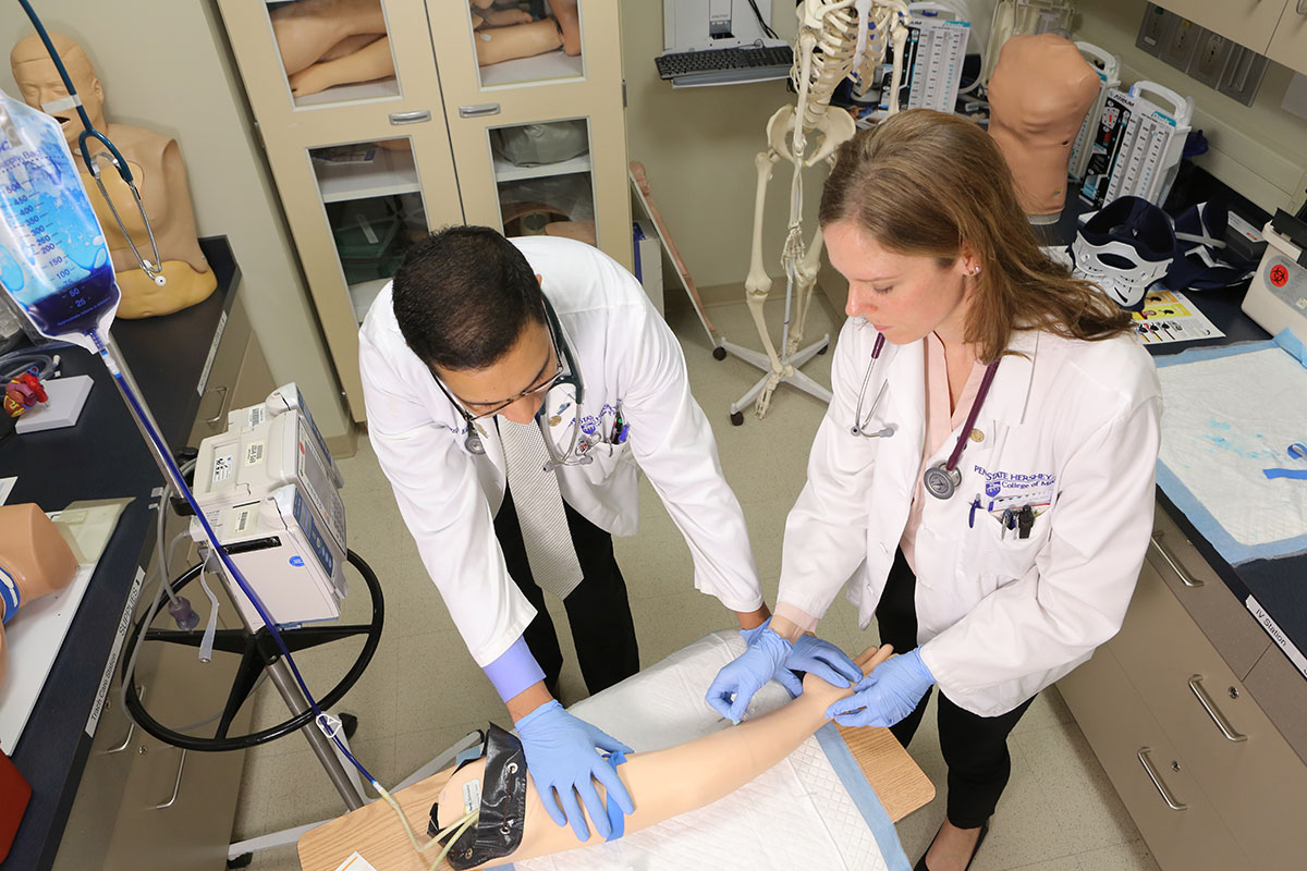 Students Zainul Hasanali and Lauren Kaminsky in the Penn State College of Medicine MD/PhD Medical Scientist Training Program practice a simulation exercise in the Penn State College of Medicine Simulation Center in April 2017. The students are seen wearing short white lab coats and blue gloves, working with a model arm, which is in the lower center of the photo with an IV bag to the left.