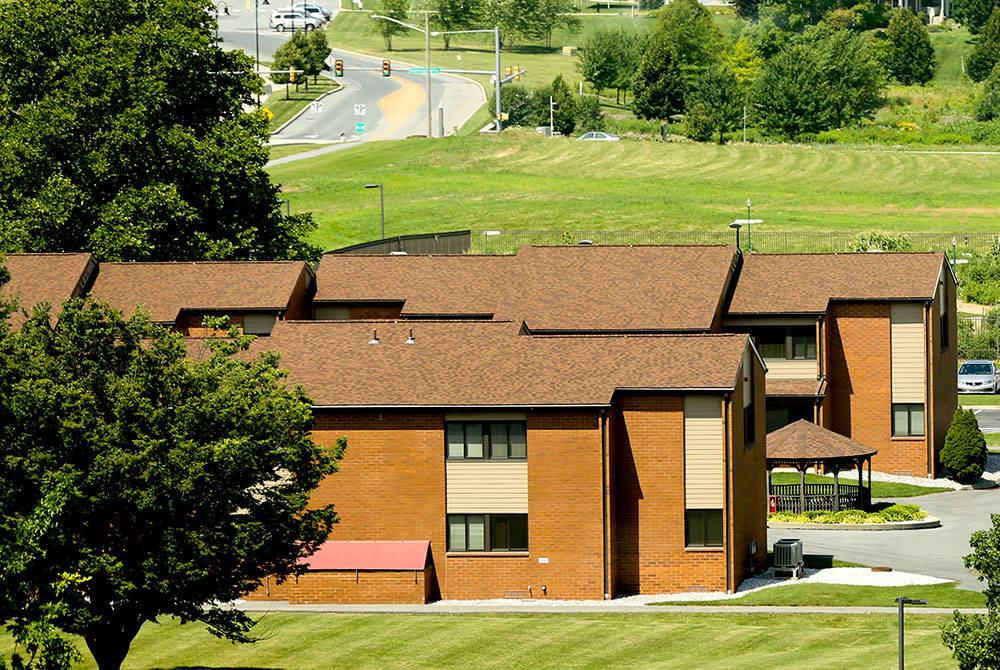 Housing is available to Penn State College of Medicine students, residents and postdocs in University Manor East and West apartment complexes. One of the complexes is pictured as seen from a higher floor of a nearby building, with a road and trees framing it in the background.