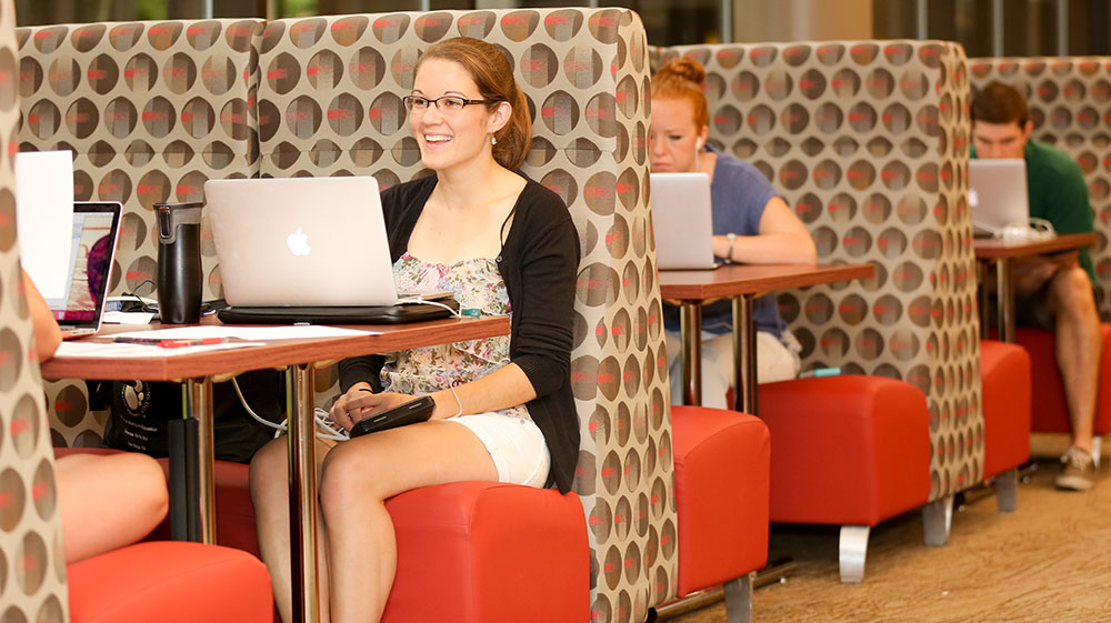 Students are seen studying in summer 2016 in the newly renovated Harrell Health Sciences Library at Penn State College of Medicine. The new study booths pictured are set up like restaurant booths, with padded seats. In the foreground, a woman studies with her laptop while talking to a woman across from her who is not visible in the picture. In the background, other students are seen studying.