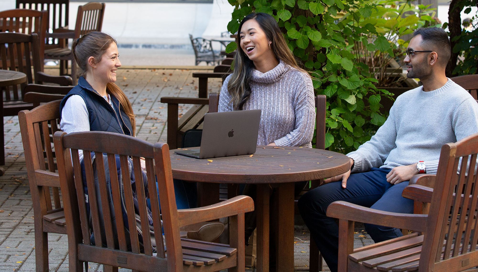 Three Penn State College of Medicine students are seen sitting in an outdoor courtyard, laughing together. A laptop is open on a table in front of them.