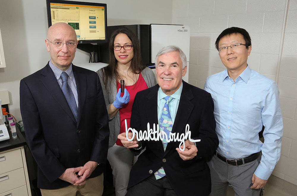 The Penn State Institute for Personalized Medicine labs offer cutting-edge genomic technologies. Key personnel from the Institute are pictured, including Director James Broach, PhD, third from left. The four people are seen standing in a lab, and Dr. Broach is holding a white sculpture of the word breakthrough. Another person is holding a laboratory sample.