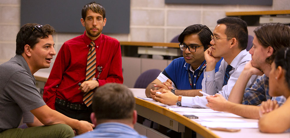 A group of medical students are seen in a lecture room, talking together. Dr. Joshua Davis of Penn State College of Medicine is seen in the back, looking over the group.