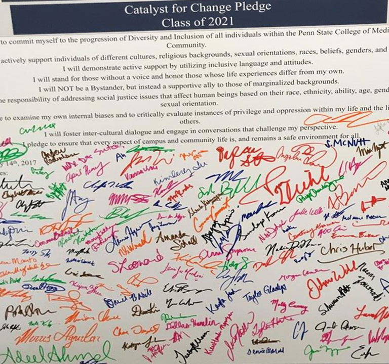 Incoming students at Penn State College of Medicine were invited to sign a Catalyst for Change pledge supporting diversity and inclusion in the College community. A large sign with the text of the pledge printed at the top is visible, with the bottom half of the sign filled with student signatures in a variety of colors. The photo was taken in 2017.