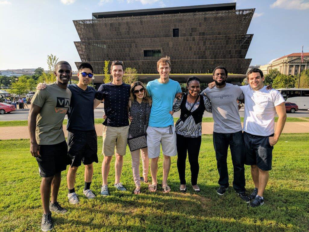Student leaders Brandon Williams, Leon Lin, Robert Fort, Pardis Pooshpas, David Booth, Felicia Cooper, Nd Ekpa and Andrew Feldman are pictured on a group trip to the National Museum of African American History in Washington, D.C. The students are representatives or leaders for Student National Medical Association, Military Medical Interest Group, PSUCOM Pride, American Medical Women Association, LAMSA and Jewish Union of Medical Professionals. The students are pictured standing on a lawn with the museum visible in the background. The photo was taken in 2017.