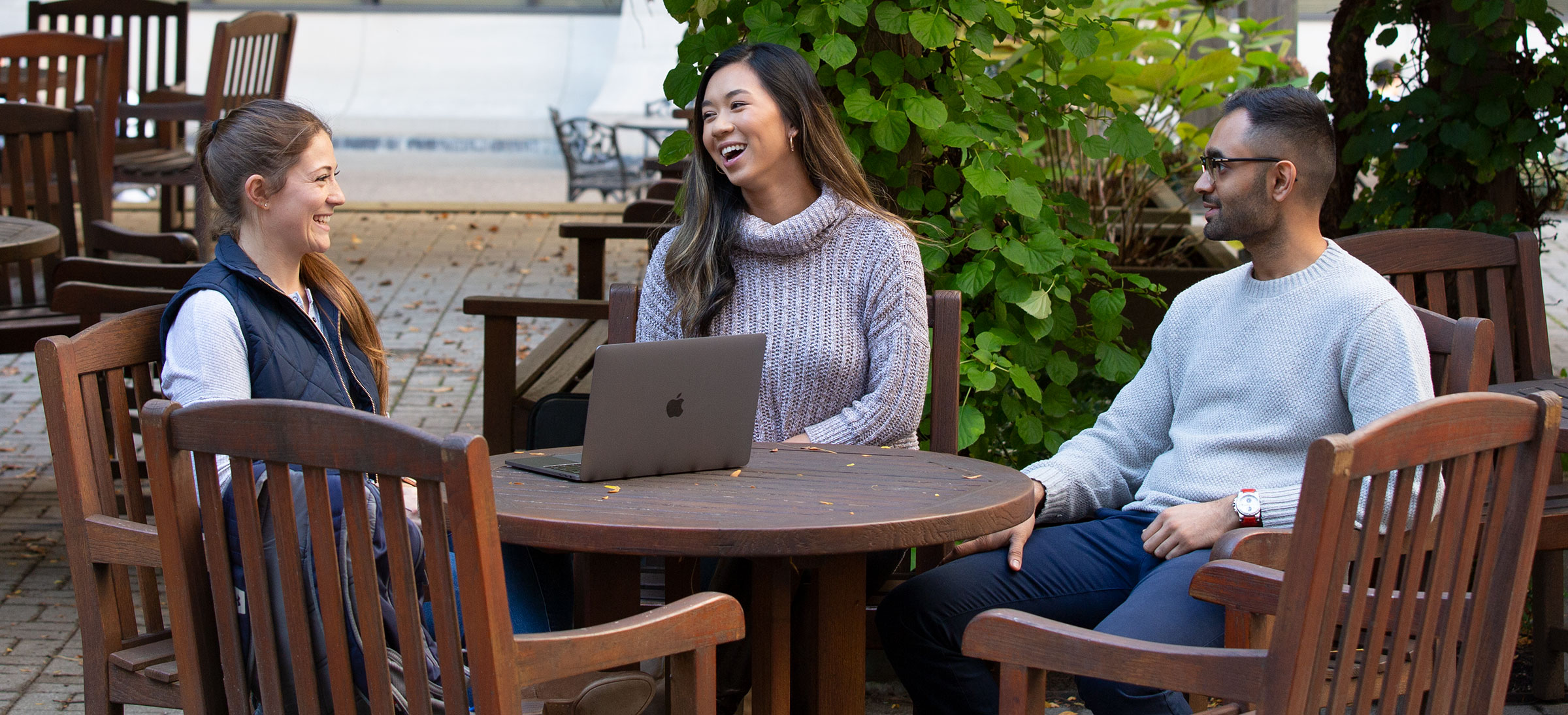 Three Penn State College of Medicine students are seen sitting in an outdoor courtyard in fall 2019, laughing together. A laptop is open on a table in front of them.