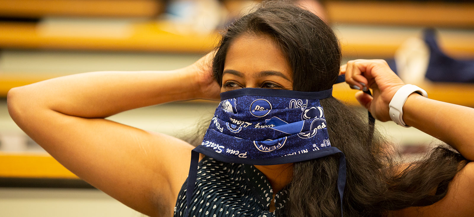 A Penn State College of Medicine medical student is seen during the 2020 orientation. She is tying a Penn State-themed mask.