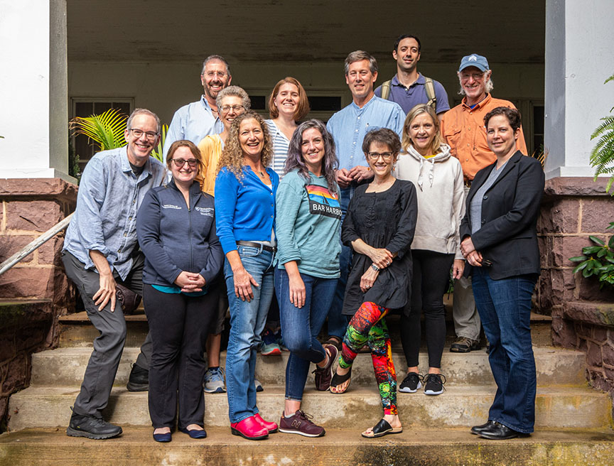 Faculty and staff of the Penn State College of Medicine Department of Humanities are pictured outdoors in November 2016. Two rows of people are standing in front of tan barn doors, and another row is sitting in front on a log wall.