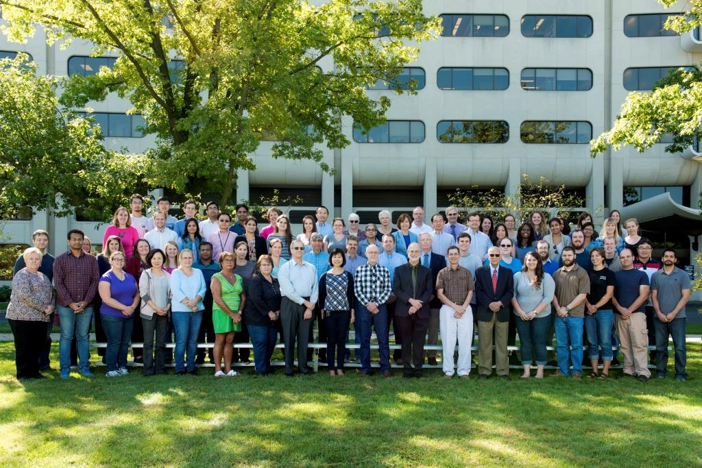 The faculty, staff, postdocs and students of the Department of Microbiology & Immunology at Penn State College of Medicine are pictured in 2016, standing in four rows outside the College.