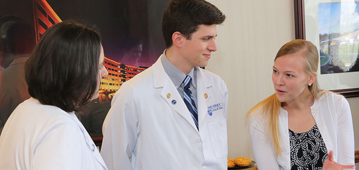 Three Family and Community Medicine students in the Family Medicine Accelerated Program at Penn State, which offers three years of medical school and three years of residency in an accelerated program, are seen having a conversation during the program entrance signing in 2016.