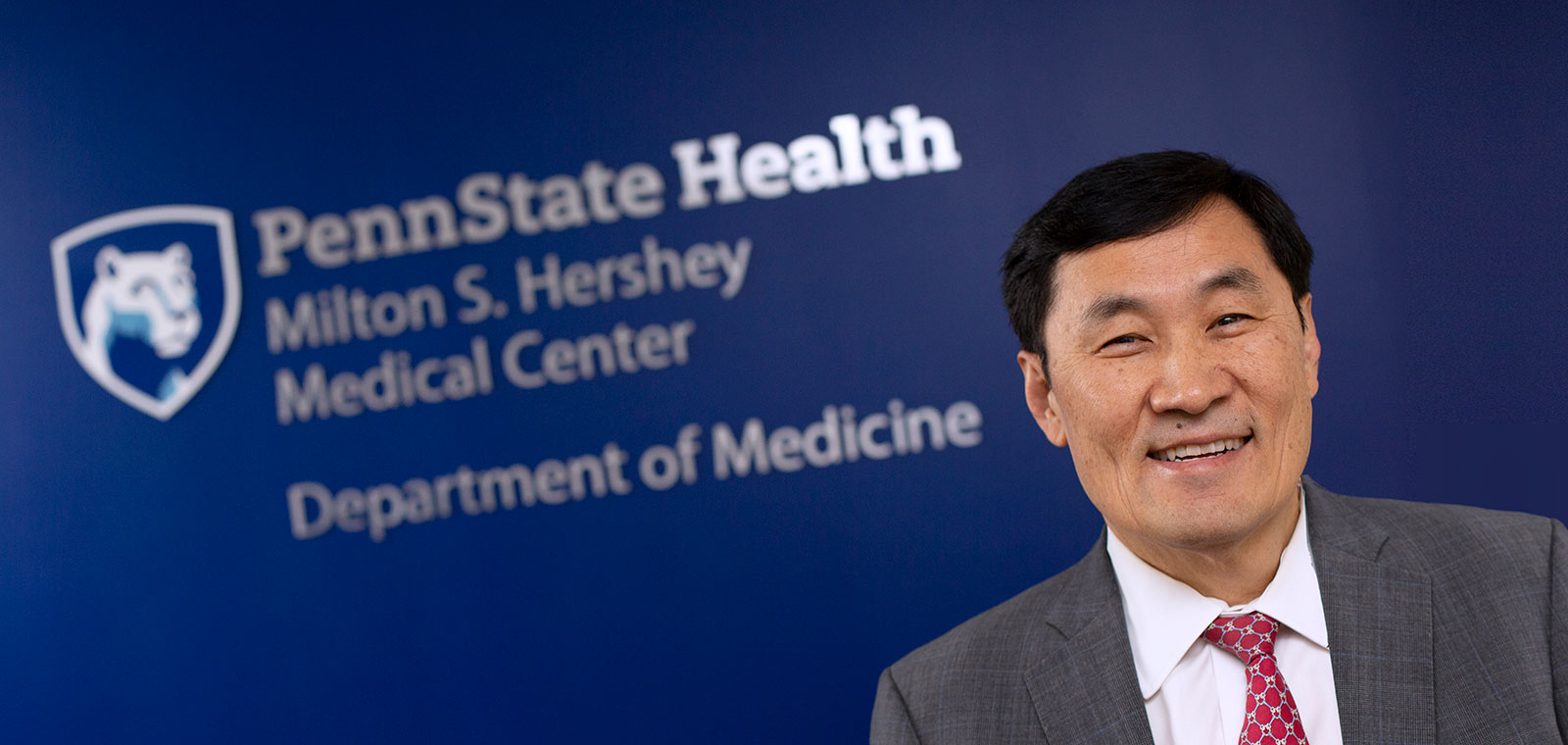 Dr. Thomas Ma, chair of the Department of Medicine at Penn State College of Medicine, is pictured in front of a blue photo backdrop with the department's logo. He is talking animatedly and looks happy.