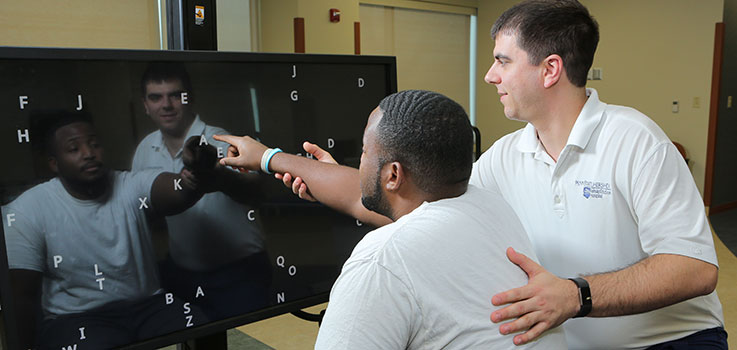 An employee of Penn State Physical Medicine and Rehabilitation works with a client at Penn State Rehabilitation Hospital in Hummelstown, PA, in early 2017. The client is seated and pointing at a digital screen with letters on it, and the employee is guiding him.
