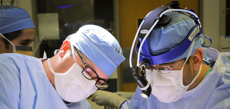 Matthew Taylor, MD, thoracic surgeon and Alok Dash, MD, fellow, thoracic surgeon at Penn State Health Milton S. Hershey Medical Center, is seen in the operating room at the Medical Center in 2016, operating the Flex robot. They are pictured wearing a surgical mask and blue surgical scrubs, with the side view of another surgeon in scrubs seen to the left of the photo.