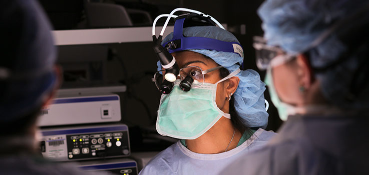 Dorothy V. Rocourt, MD, surgeon at Penn State Health Milton S. Hershey Medical Center, is seen in the operating room at the Medical Center in October 2014. She is pictured wearing a surgical mask and blue surgical scrubs, with the back of another surgeon in scrubs seen to the right of the photo.