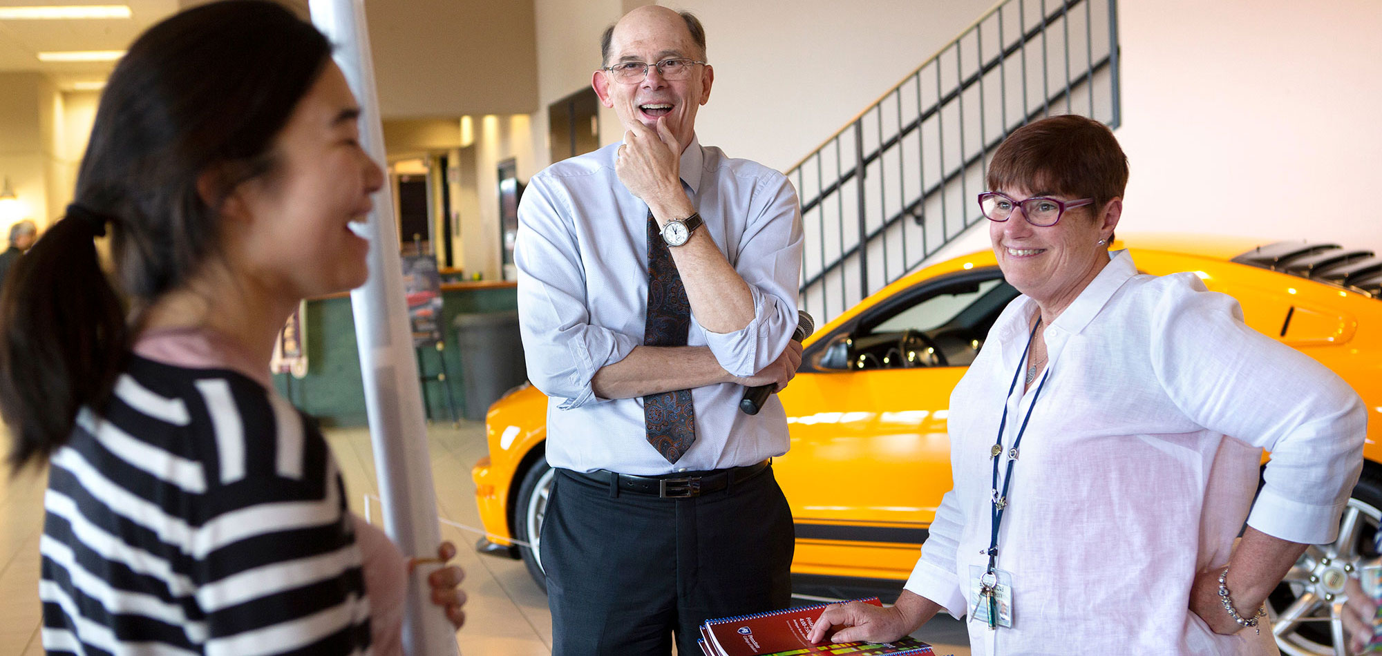 A graduate student is seen laughing with Dr. Charles Lang, Associate Dean for Graduate Education, center, and Kathy Simon, Director of Graduate Education, right, at the 2018 Faculty and Student Research Retreat. The three are pictured standing in front of a car in a museum.