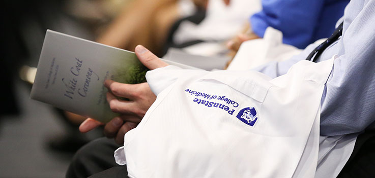 A closeup of the Penn State College of Medicine logo is seen on the jacket of a white coat, draped over the arm of a medical student who is also holding a White Coat Ceremony program. The student was part of the July 2016 White Coat Ceremony, in which incoming medical students at the College receive their short white coats signifying their status as future doctors.