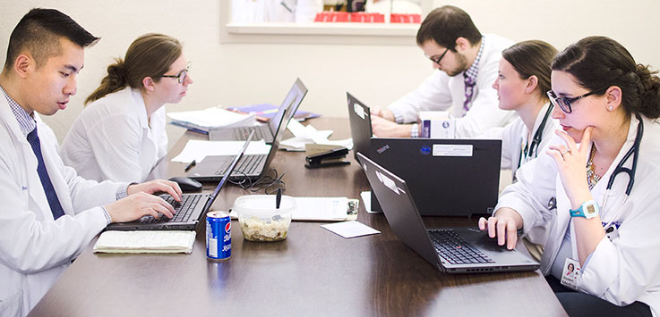 Medical students at Penn State College of Medicine are seen sitting around a table in their white coats, working at laptops, depicting the administrative aspects of the healthcare process.