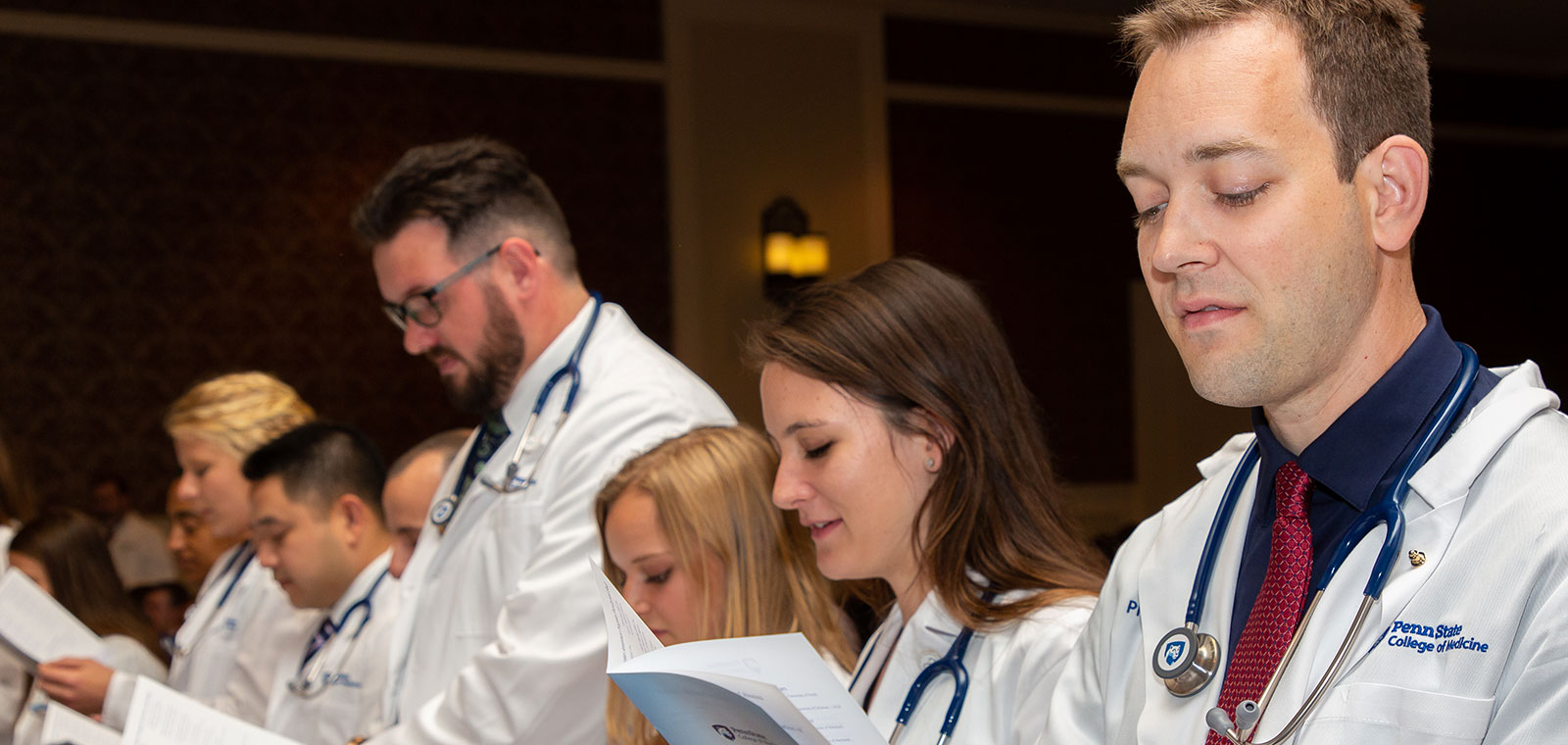 Students in the Physician Assistant Program at Penn State College of Medicine take part in the White Coat Ceremony in 2016, during which the students receive their white coats signifying the start of their training. Three female students are seen in the foreground, reading from the event program, with a male and female student visible in the background.