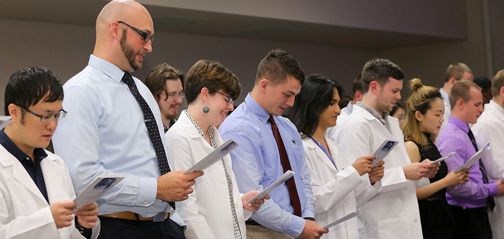 Penn State graduate students, including those from the Department of Public Health Sciences, participate in the ninth annual Graduate Student Oath Ceremony on August 18, 2017. The students are pictured standing in a line, reading from a program.