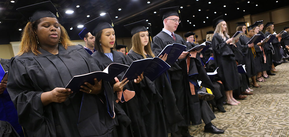 Penn State graduate students from the Department of Public Health Sciences attend the College of Medicine Commencement Ceremony at the Hershey Lodge on May 20, 2018. The students are pictured standing in caps and gowns, holding programs.
