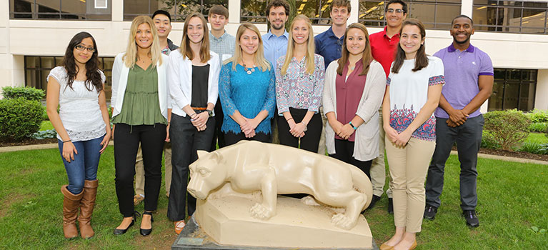 Students from the 2017 SURIP (Summer Undergraduate Research Internship Program) at Penn State College of Medicine are pictured standing near the statue of the Nittany Lion in the College courtyard. An academic building and grass can be seen behind the group of more than 10 students.