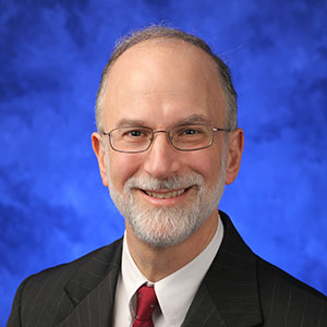 Aron Lukacher, MD, PhD, is Chair of the Department of Microbiology and Immunology at Penn State College of Medicine. He is pictured in a dark suit jacket and red tie against a blue background.