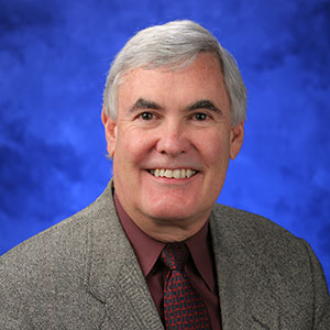 James Broach, PhD, is Chair of the Department of Biochemistry and Molecular Biology at Penn State College of Medicine. He is pictured in a tan suit jacket, maroon shirt and dark tie against a blue background.
