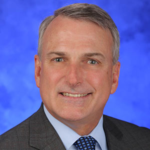 Kent Vrana, PhD, is Chair of the Department of Pharmacology at Penn State College of Medicine. He is pictured in a dark suit jacket, light blue shirt and blue patterned tie against a blue background.