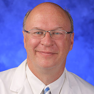 Mack Thomas Ruffin IV, MD, is Chair of the Department of Family and Community Medicine at Penn State College of Medicine. He is pictured wearing a white dress shirt and dark tie, as well as a white medical coat, in front of a blue photo background.