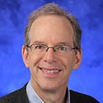 Michael Green, MD, MS, is interim chair of the Department of Humanities at Penn State College of Medicine. He is pictured wearing a collared shirt, suit jacket and tie, in front of a blue photo background.