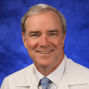 Peter Dillon, MD, MSc, is Chair of the Department of Surgery at Penn State College of Medicine. He is pictured in a white dress shirt, blue patterned tie and white medical coat against a blue background.