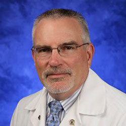 Ronald Wilson, VMD, MS, DACLAM, is Chair of the Department of Comparative Medicine at Penn State College of Medicine. He is pictured in a white lab coat, light blue shirt and light blue patterned tie against a blue background.