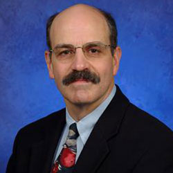 Vernon Chinchilli, PhD, is Chair of the Department of Public Health Sciences at Penn State College of Medicine. He is pictured in a black suit jacket, light blue shirt and red patterned tie against a blue background.