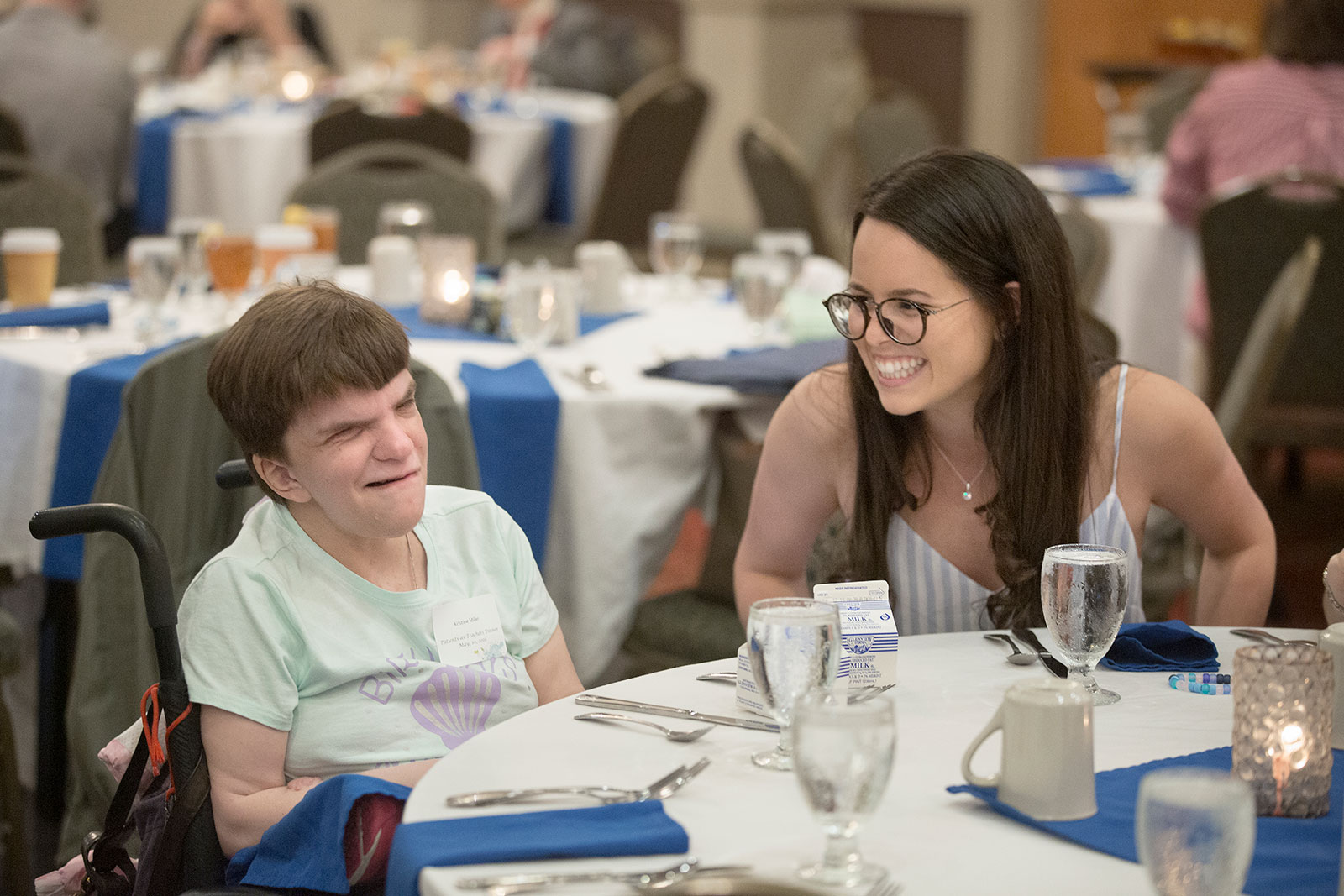 A young woman is seen talking happily with a woman in a wheelchair sitting at a table with her.